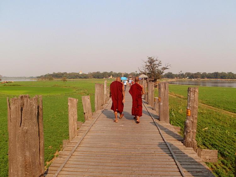 Monks on the teak bridge in Amarapura, one of the old capitals in Mandalay, Myanmar
