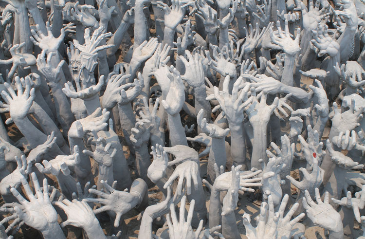 Outstretched hands at Wat Rong Khun, the white temple in Chiang Rai, Thailand