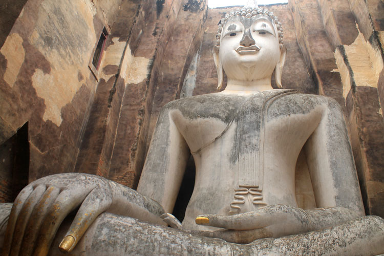 Cycling between Ancient Ruins in Sukhothai, Thailand -- A huge seated Buddha statue
